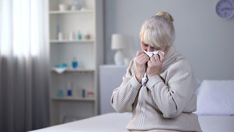 深深地哭泣在康复中心,健康问题的沮丧的年长妇女 免版税图库摄影
