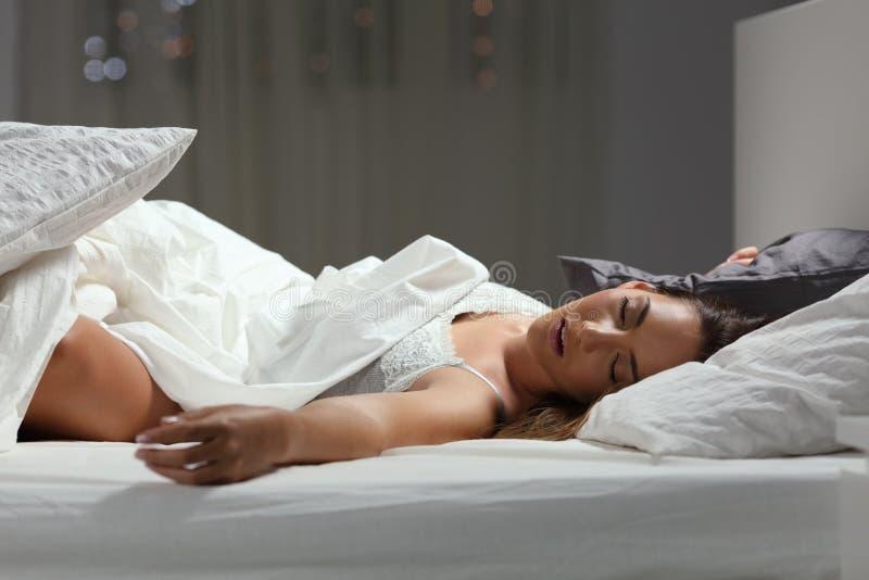 深深地在家睡觉夜的妇女 免版税图库摄影