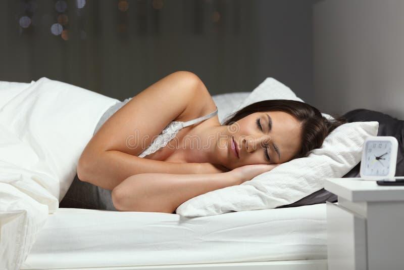 深深地睡觉在一张床上的妇女夜 免版税库存照片