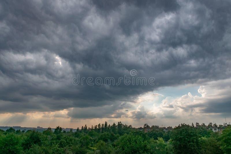 深灰云彩盘旋了在城市 日落 库存照片