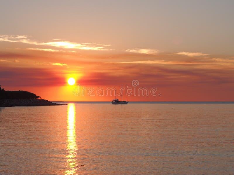 深红日落和帆船在Fannie咆哮 库存图片