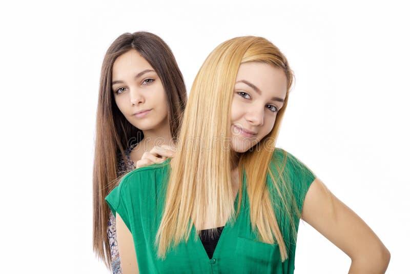 深色两个可爱的十几岁的女孩画象-白肤金发和 免版税库存照片