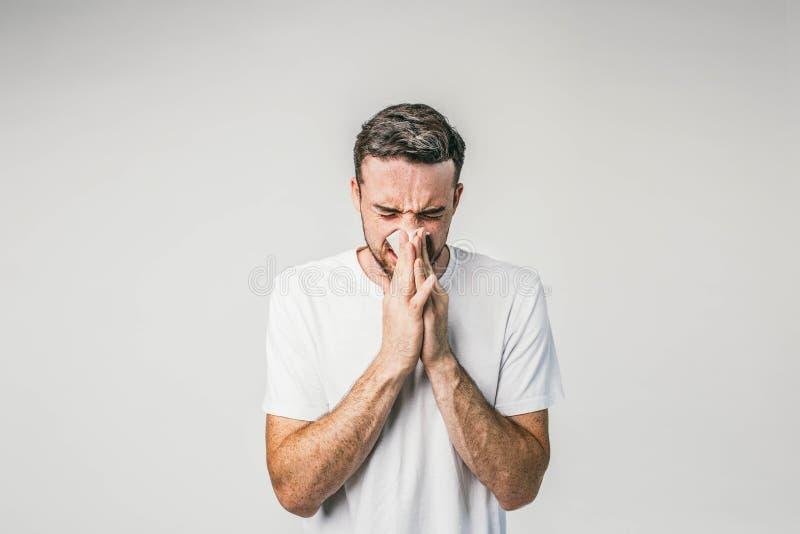 深色头发的人在白色墙壁附近站立并且打喷嚏 如他得了一些寒冷和很快非常不适,似乎 库存照片