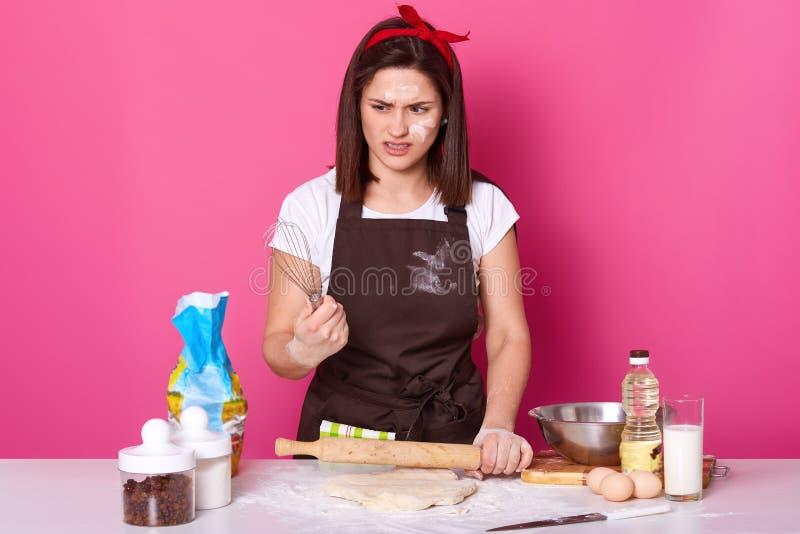 深色头发的女孩画象围裙的弄脏用面粉,T恤杉和红色发带,在手上站立与飞奔并且感到恶心 免版税库存图片