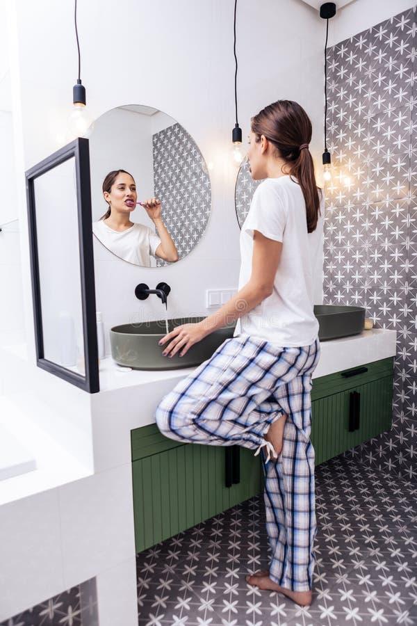 深色头发的妇女掠过的牙在她明亮的现代卫生间里 免版税图库摄影