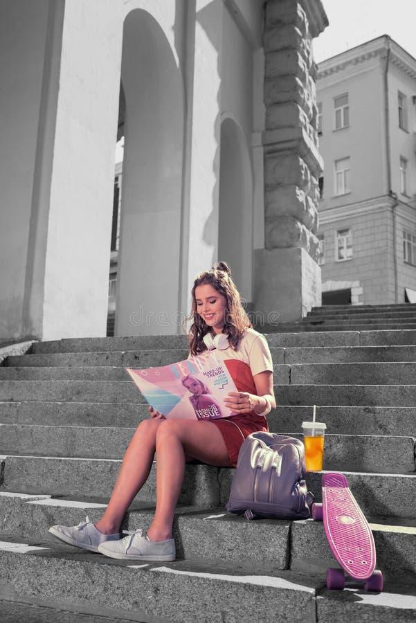 深色头发的放光的学生感觉在类以后休息了读书秀丽杂志 免版税库存图片