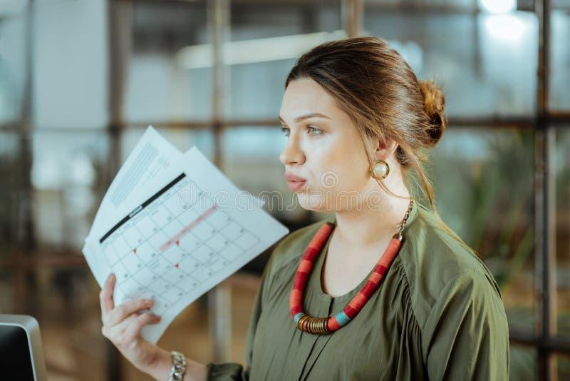 深色头发的空气妇女感觉的短小在工作以后在办公室 免版税库存图片