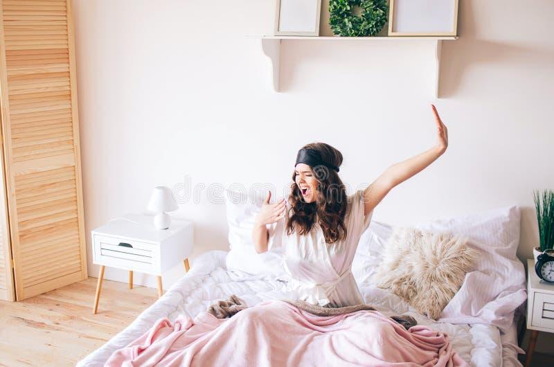 深色头发的美丽的年轻浅黑肤色的男人醒在她的床上 舒展ahnd和哈欠 单独在卧室 睡觉面具  库存图片