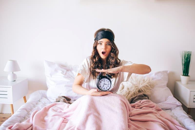 深色头发的美丽的年轻浅黑肤色的男人醒在她的床上 迷茫的妇女举行时钟在手上 以后醒了 惊奇模型 库存照片