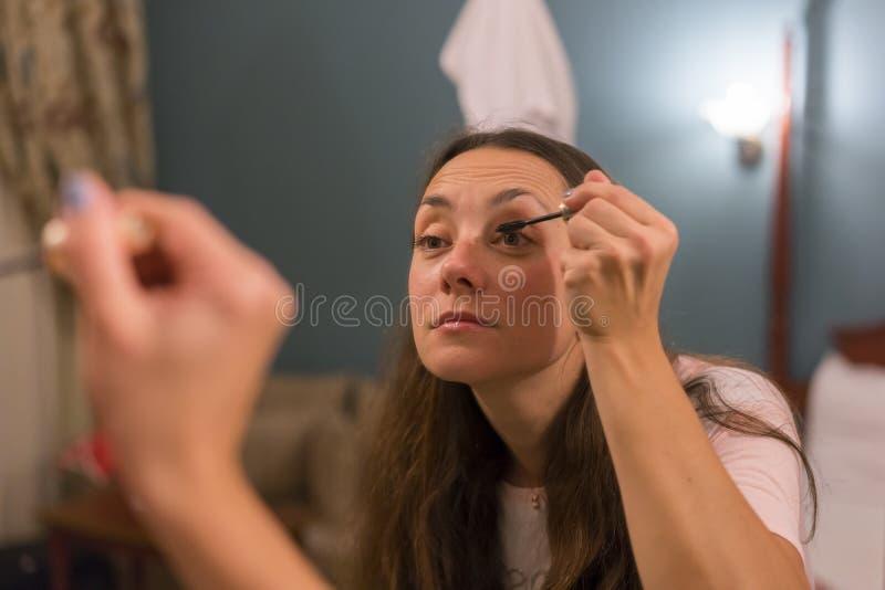 深色妇女申请组成& x28;绘她的eyelashes& x29;在镜子前面的一个平衡的日期 在她的反射的焦点 库存照片