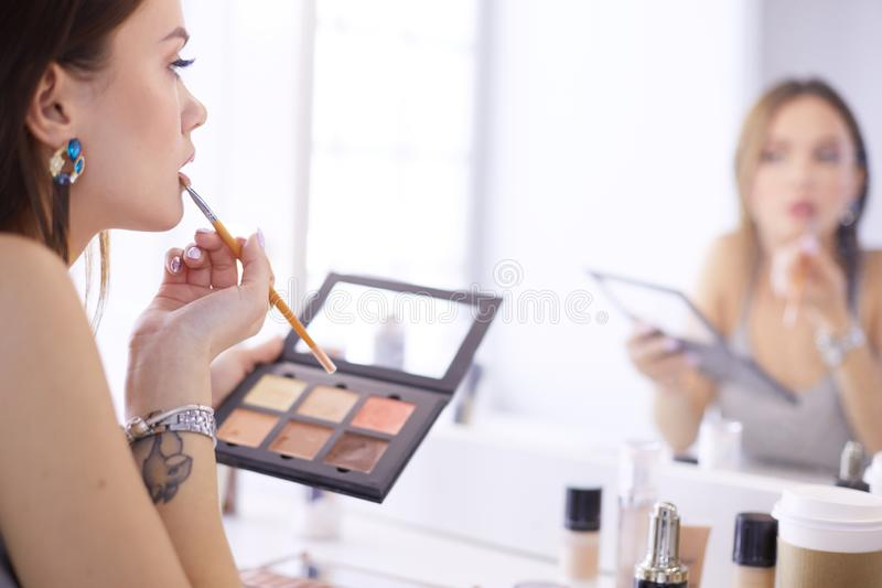 深色妇女申请补偿在镜子前面的一个平衡的日期 免版税图库摄影