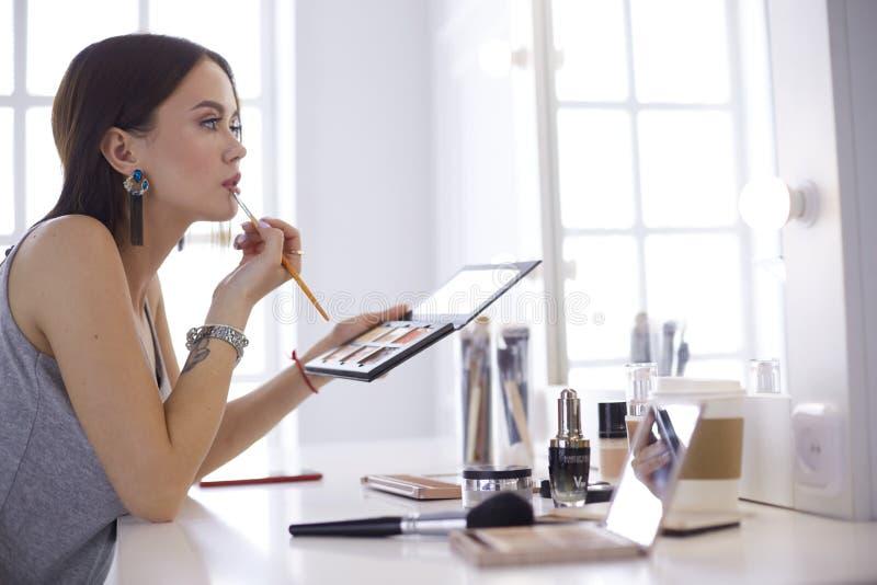 深色妇女申请补偿在镜子前面的一个平衡的日期 库存图片