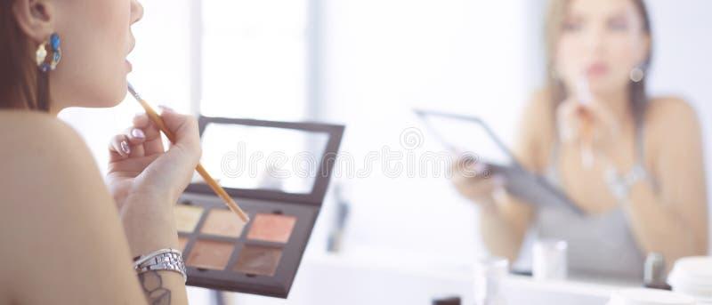 深色妇女申请补偿在镜子前面的一个平衡的日期 免版税库存图片