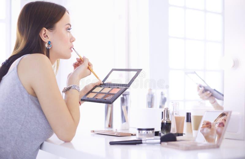 深色妇女申请补偿在镜子前面的一个平衡的日期 免版税库存照片