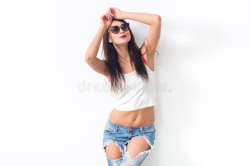 年轻深色式样摆在,拿着太阳镜,佩带的被剥去的牛仔裤和穿甲,演播室在白色背景射击了,没有 免版税库存照片