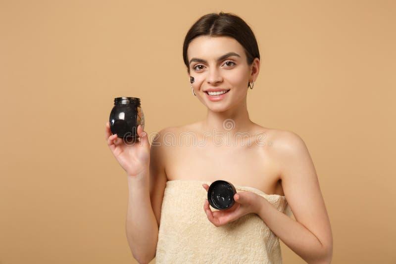 深色的一半的关闭有完善的皮肤的赤裸妇女20s,裸体在米黄淡色墙壁组成被隔绝的黑面具 库存照片
