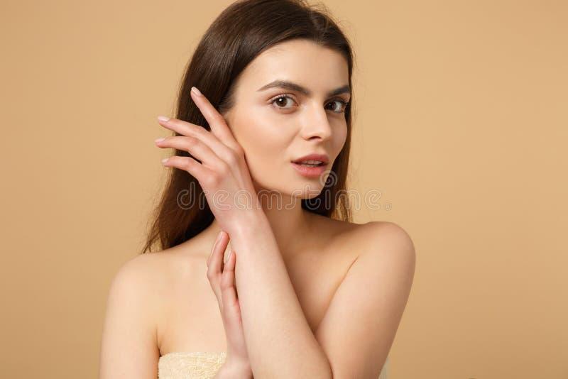 深色的一半的关闭有完善的皮肤的赤裸妇女20s,裸体在米黄淡色墙壁背景,演播室做隔绝 免版税库存图片