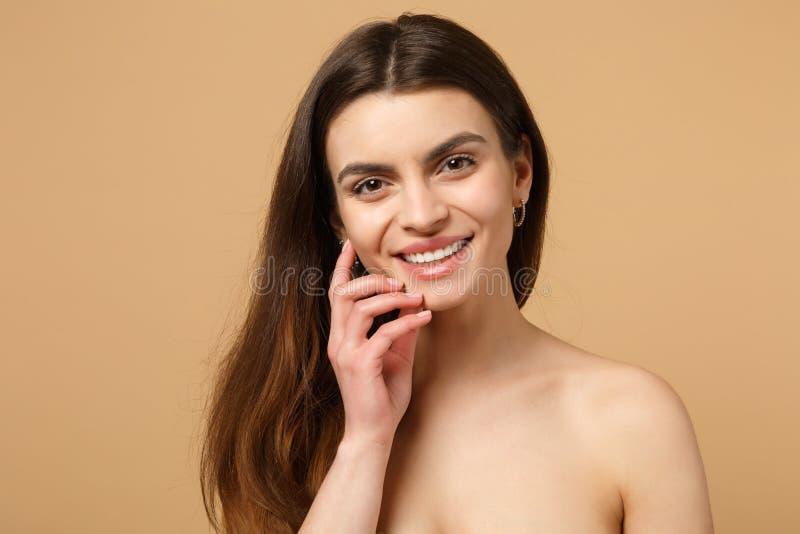 深色的一半的关闭有完善的皮肤的赤裸妇女20s,裸体在米黄淡色墙壁背景,演播室做隔绝 库存照片