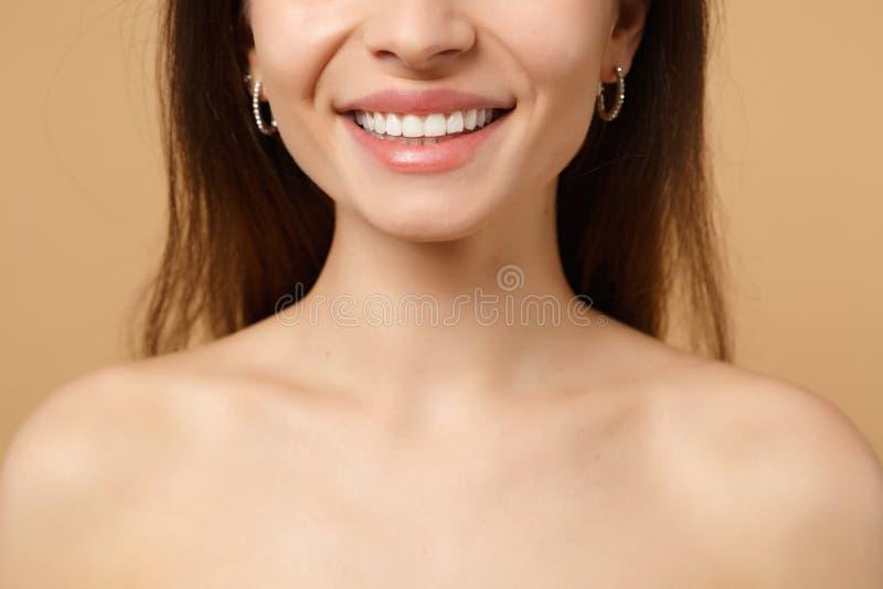 深色的一半的关闭有完善的皮肤的赤裸妇女20s,裸体在米黄淡色墙壁背景,演播室做隔绝 免版税图库摄影
