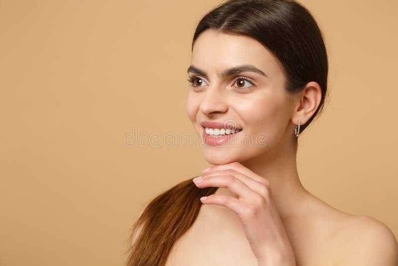 深色的一半的关闭有完善的皮肤的赤裸妇女20s,裸体在米黄淡色墙壁背景,演播室做隔绝 免版税库存照片