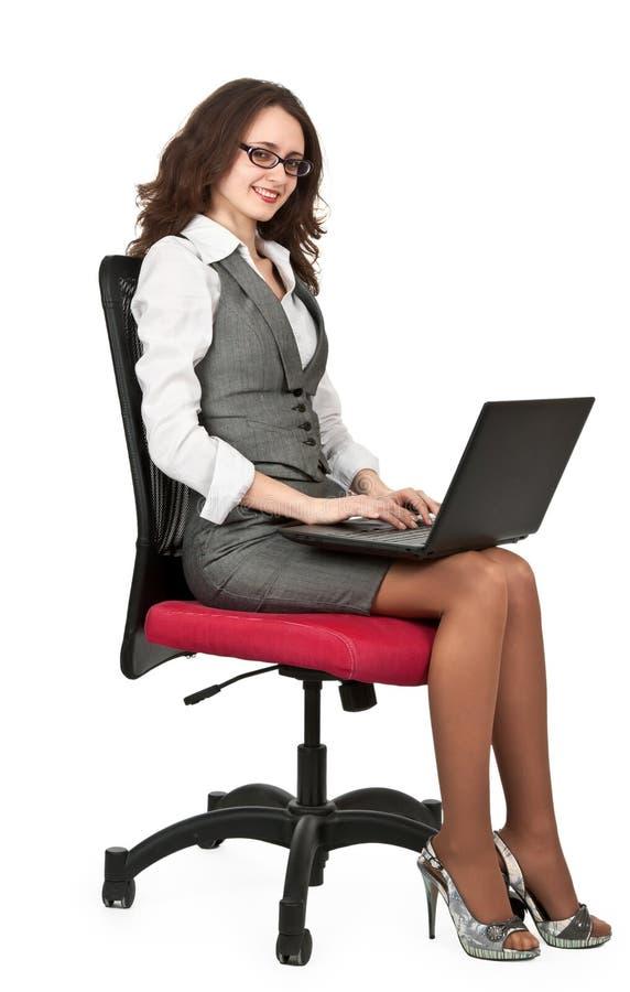 深色的企业椅子女孩膝上型计算机 库存照片