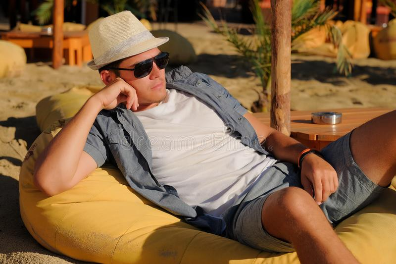 深色的在海滩咖啡馆的人佩带的草帽sleepng 免版税库存照片