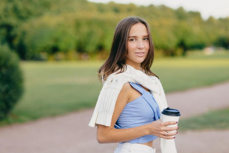 深色的夫人水平的射击有微小的身体的,穿戴在T恤杉,在肩膀的白色毛线衣,饮料芳香咖啡,站立ou 库存图片