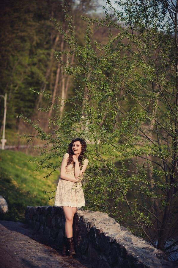 深色的女孩在桥梁站立在水附近 免版税库存图片