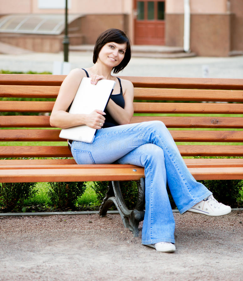 深色的女孩坐在一条长凳的一个晴天在公园与 免版税库存照片