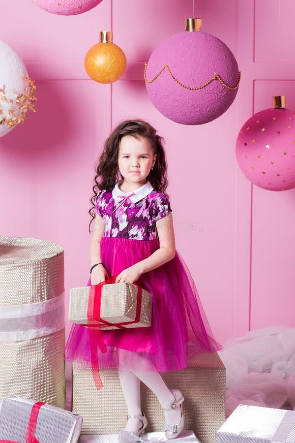 深色的女孩孩子在一件桃红色礼服的5岁 在假日有礼物的蔷薇石英室 免版税库存图片