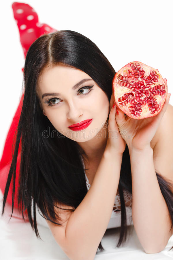 深色的女孩用石榴石果子在演播室 免版税库存照片