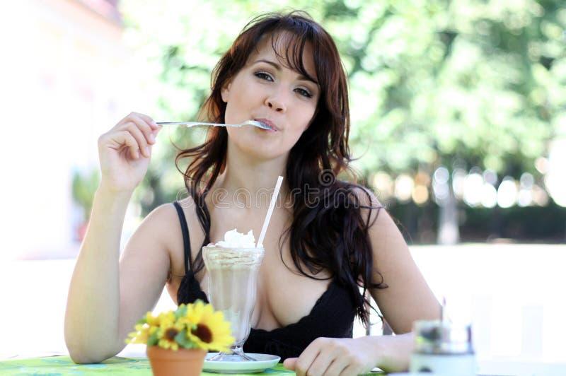 深色的奶油色冰舔匙子妇女年轻人 免版税图库摄影