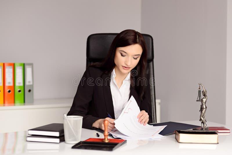 深色的妇女公证人读书和签署的遗嘱 免版税图库摄影