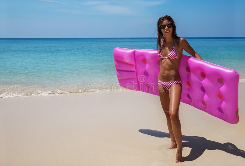 深色的妇女太阳镜晒日光浴与在热带海滩的气垫 免版税库存照片