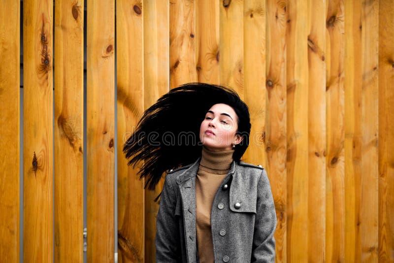 深色的妇女室外与炸毁头发 免版税库存照片
