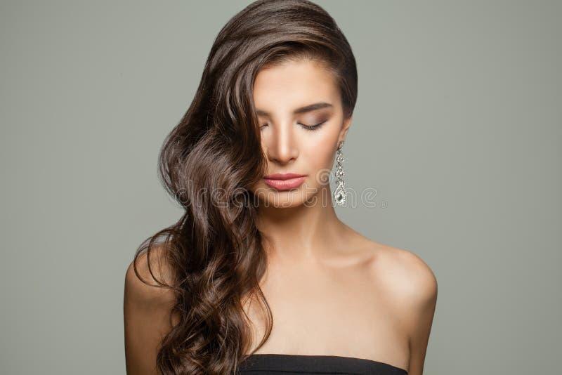 深色的妇女时尚画象有长的卷发、构成和金刚石首饰耳环的 免版税库存图片