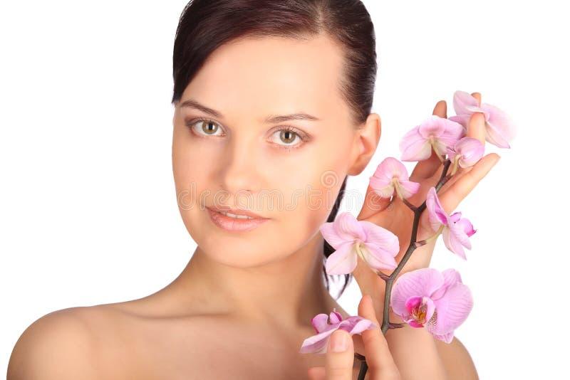 年轻深色的妇女的美丽的面孔有健康皮肤和桃红色兰花的 库存照片