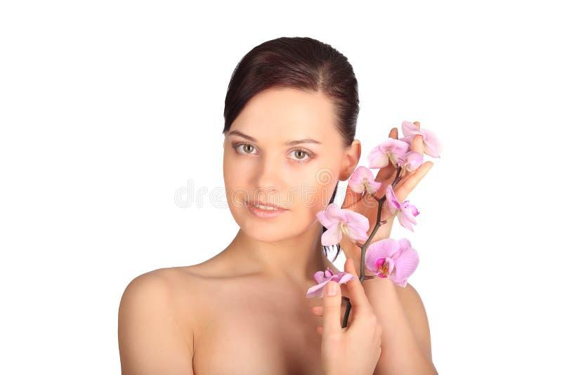 年轻深色的妇女的美丽的面孔有健康皮肤和桃红色兰花的 库存图片