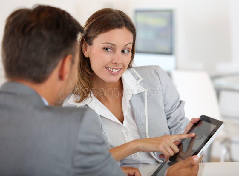 深色的妇女谈话与投资者 图库摄影