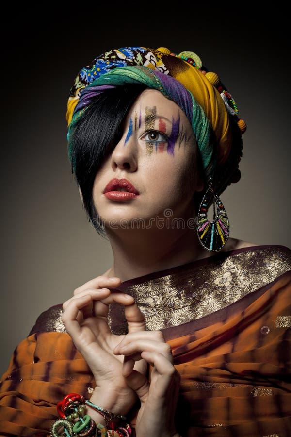 年轻深色的妇女画象有时尚构成的在褐色 免版税库存照片