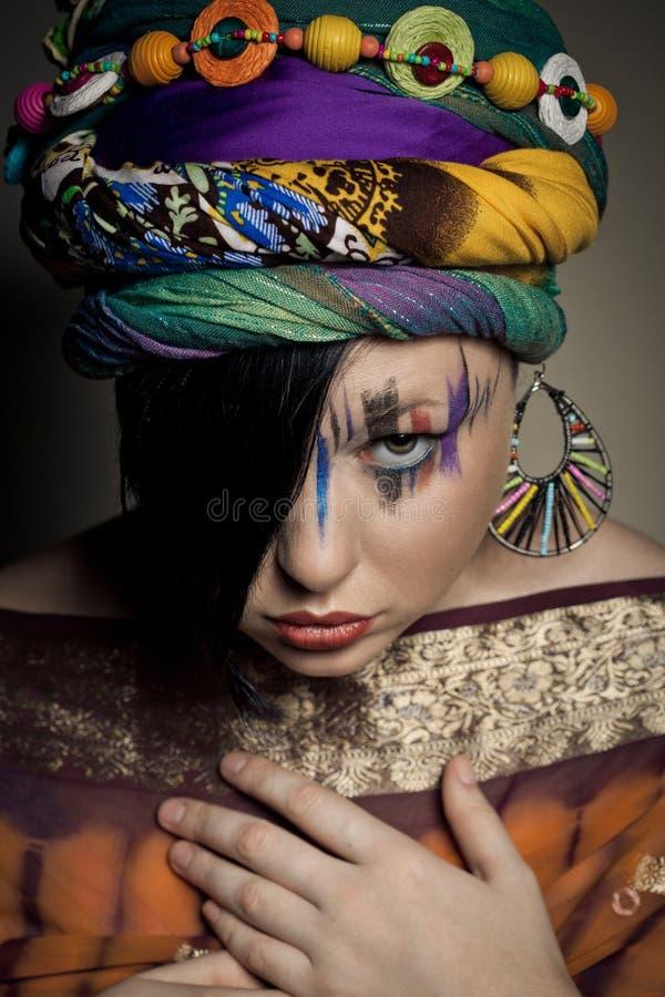 年轻深色的妇女画象有时尚构成的在褐色 图库摄影