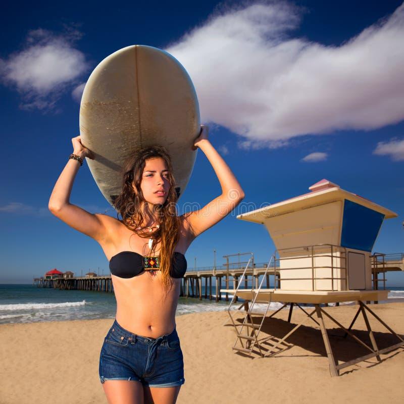 深色的拿着在海滩的冲浪者青少年的女孩冲浪板 免版税库存照片