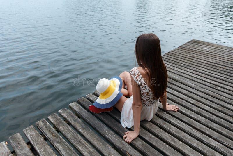 深色的白种人妇女单独坐在一件短的白色礼服的一座桥梁 免版税库存照片