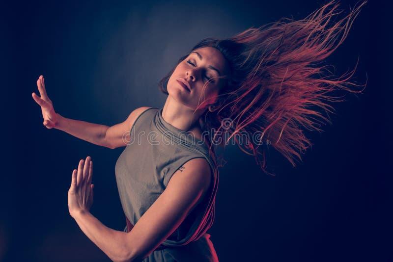 年轻深色的白种人妇女流经空气的跳舞和她的头发 库存图片