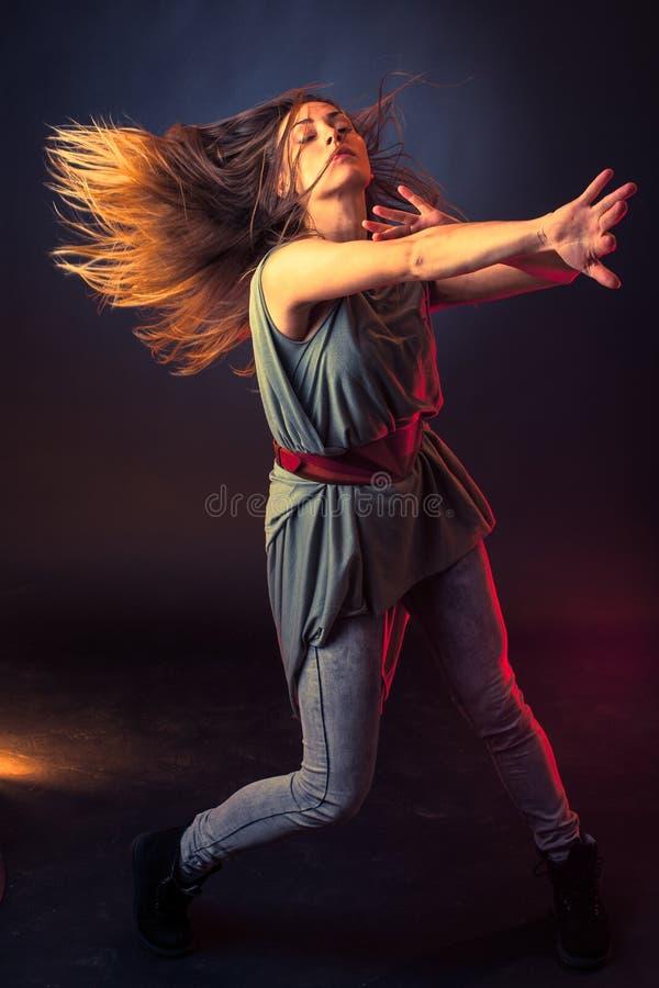 年轻深色的白种人妇女流经空气的跳舞和她的头发 免版税库存图片