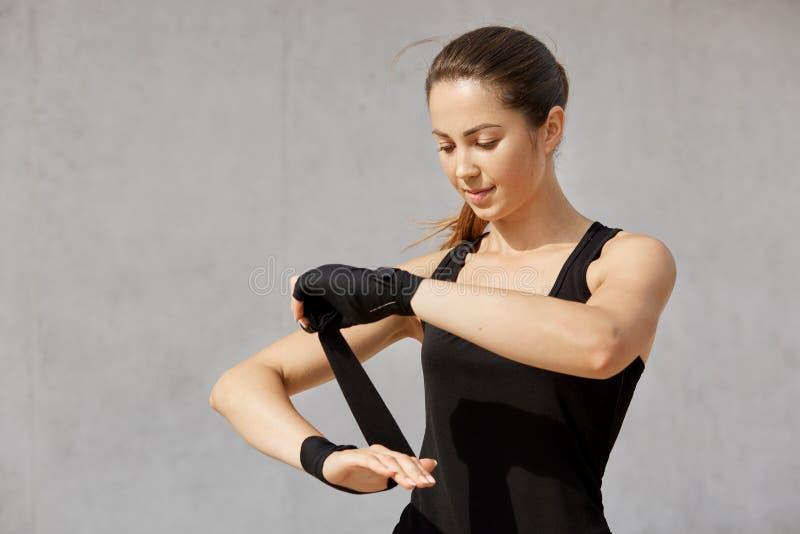 深色的运动的妇女半身照片有马尾辫的,佩带的黑成套装备,包裹腕子绷带,站立反对灰色 免版税库存照片