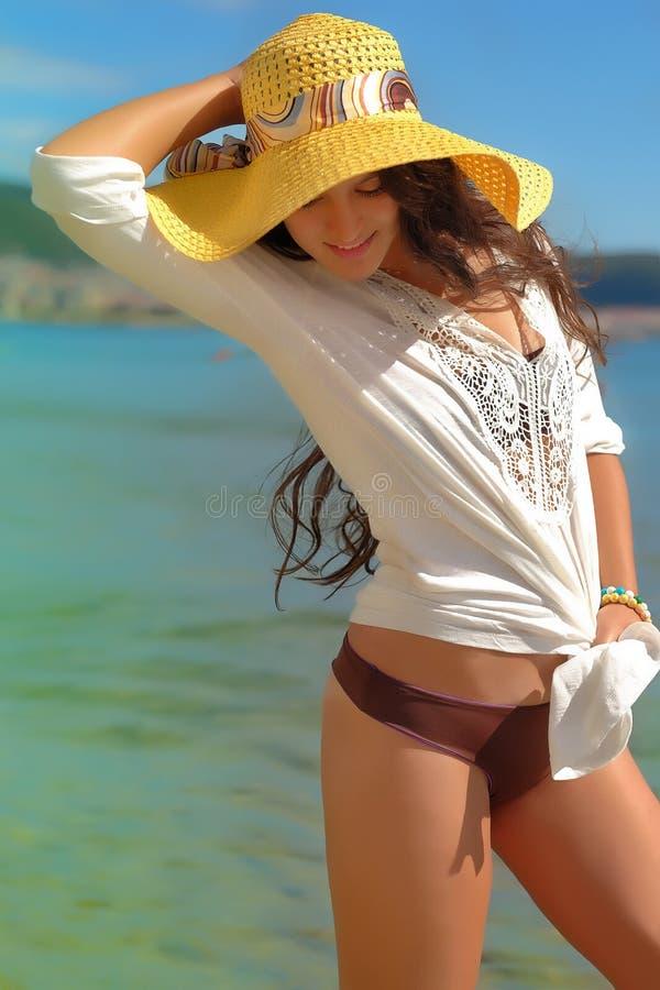 深色的lond在海滨的头发的女孩摆在和havnig乐趣 免版税库存图片
