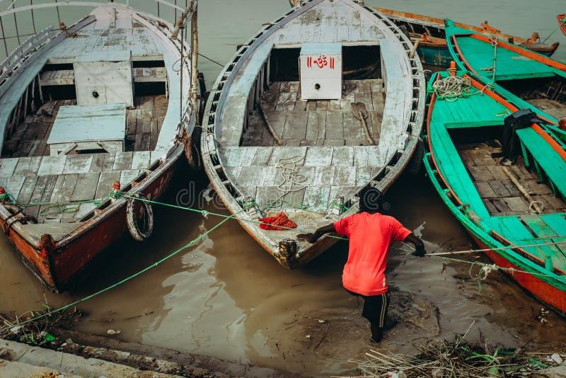 深色皮肤的人牵索被栓对一个泥泞的湖停放的小船 免版税库存图片