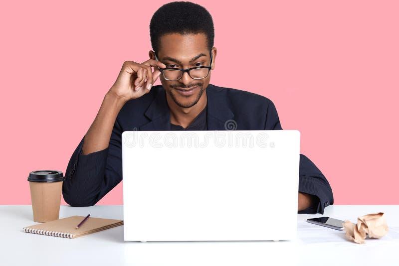 深色皮肤的人画象与膝上型计算机一起使用 英俊的黑男性坐在书桌穿着衣服,接触他的眼镜用手, 免版税库存照片