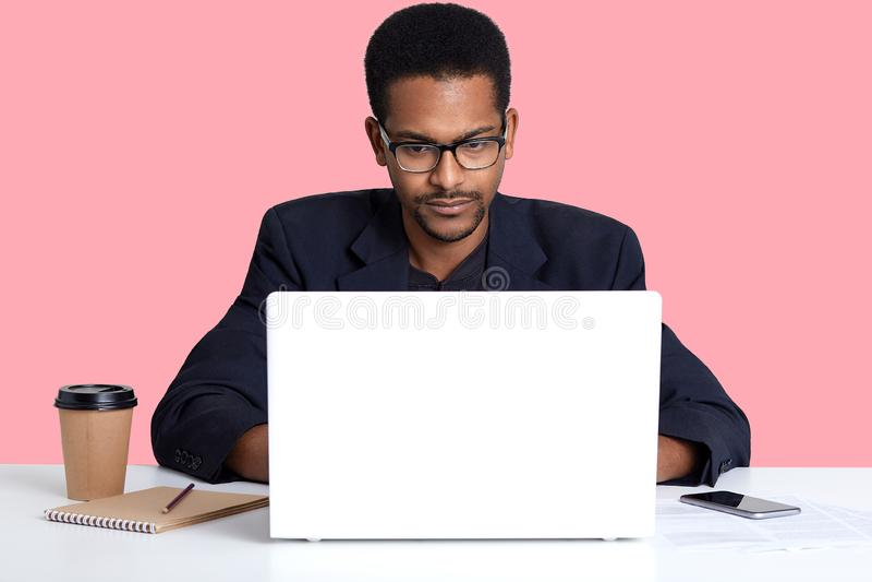 深色皮肤的男性接近的画象穿着黑衣服,在网上与膝部上面一起使用,非裔美国人的自由职业者坐在白色 免版税库存图片